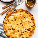 Cute pie with star design on top crust served with pile of plates and forks and a cup of coffee, striped linen