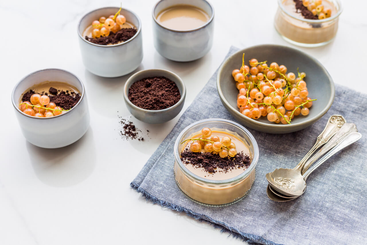 Cups of coffee panna cotta garnished with fresh white currants and Oreo cookie crumbs served on a blue chambray linen with spoons