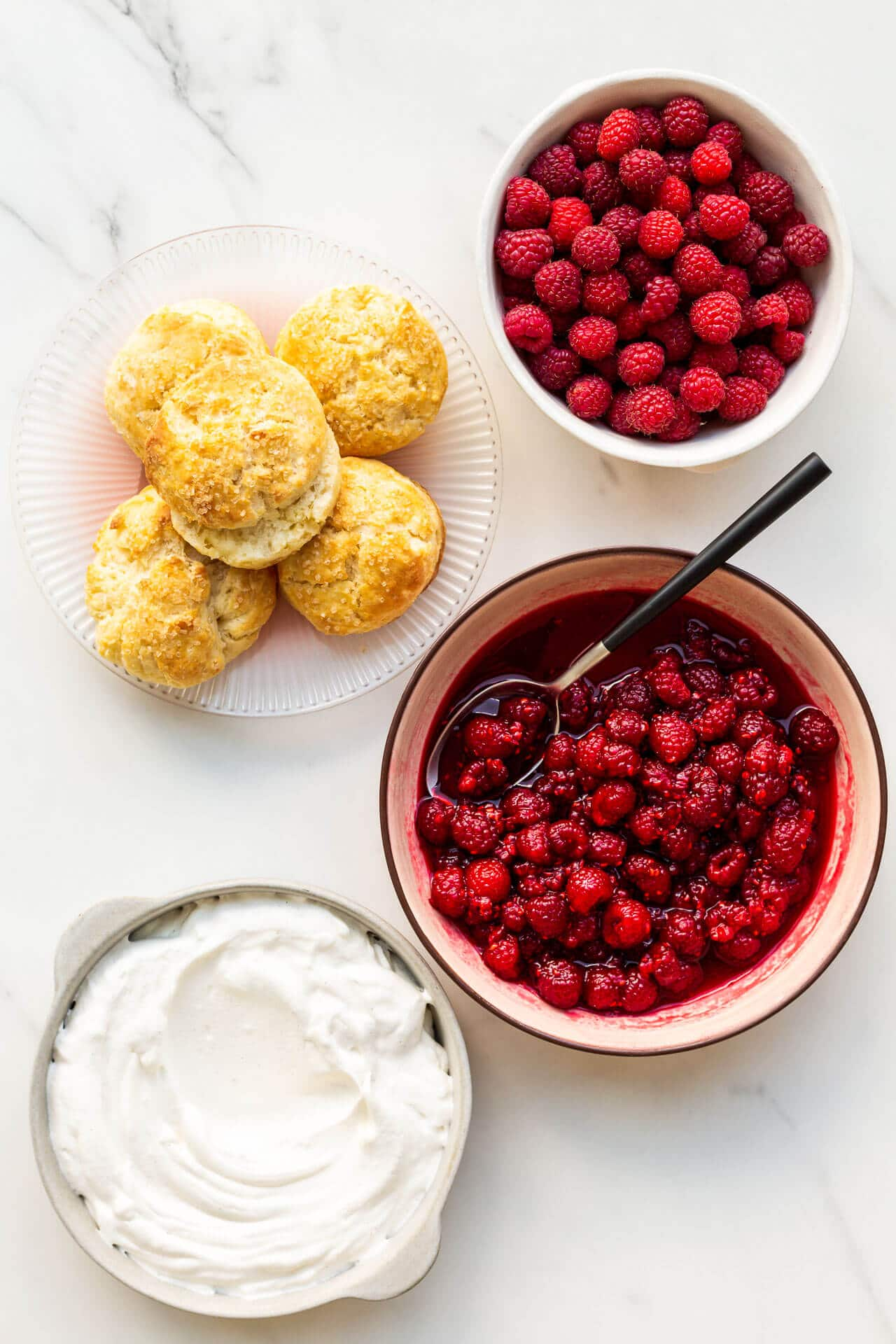 Ingredients to make raspberry shortcake are homemade biscuits, whipped cream, and macerated raspberries