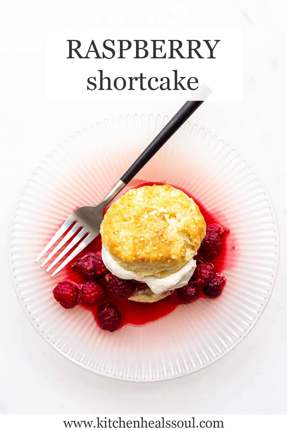 A raspberry shortcake on a pink plate with macerated raspberries and whipped cream served on a golden brown biscuit