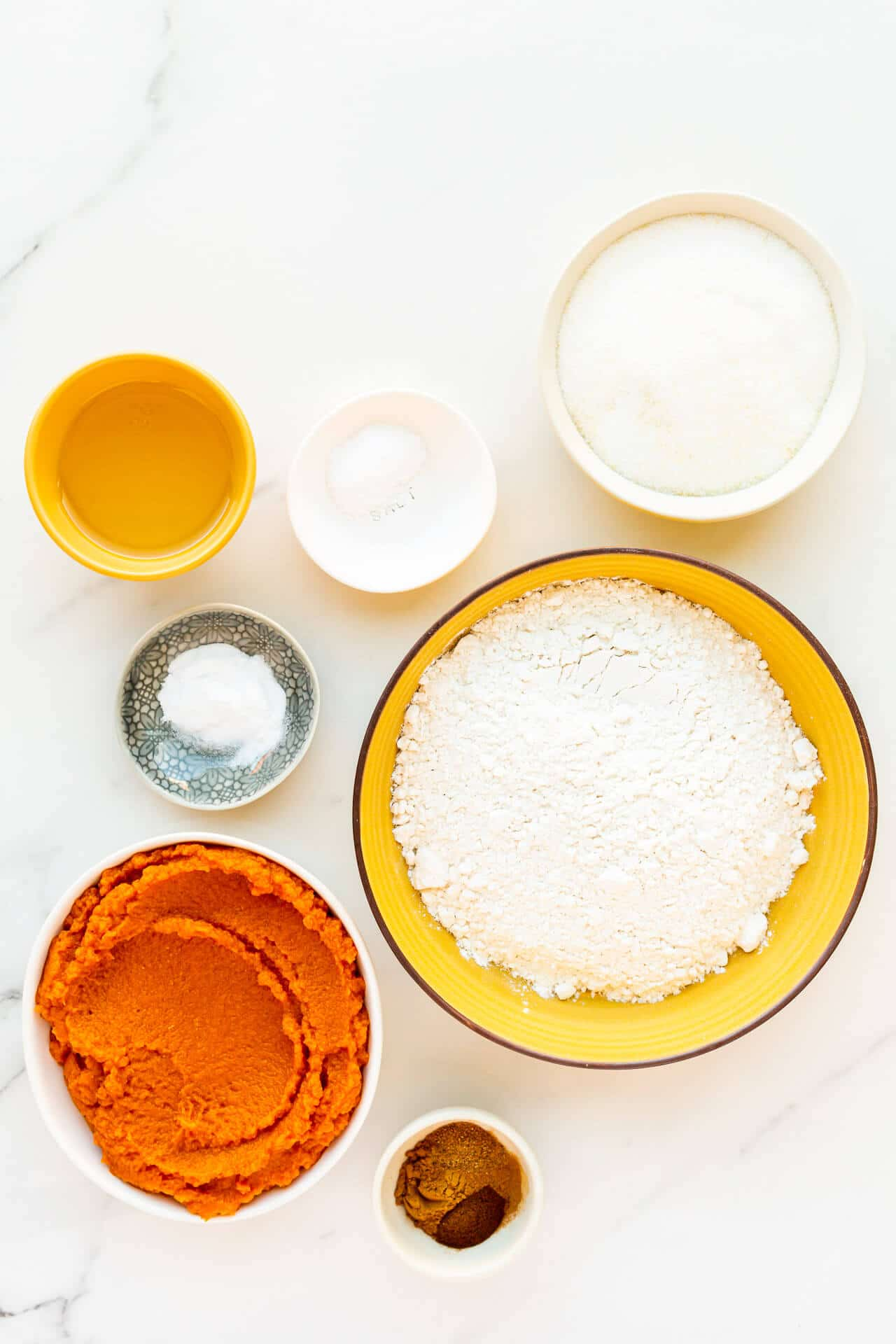 Ingredients to make eggless pumpkin bread include oil, salt, baking soda, sugar, flour, canned pumpkin, and spices