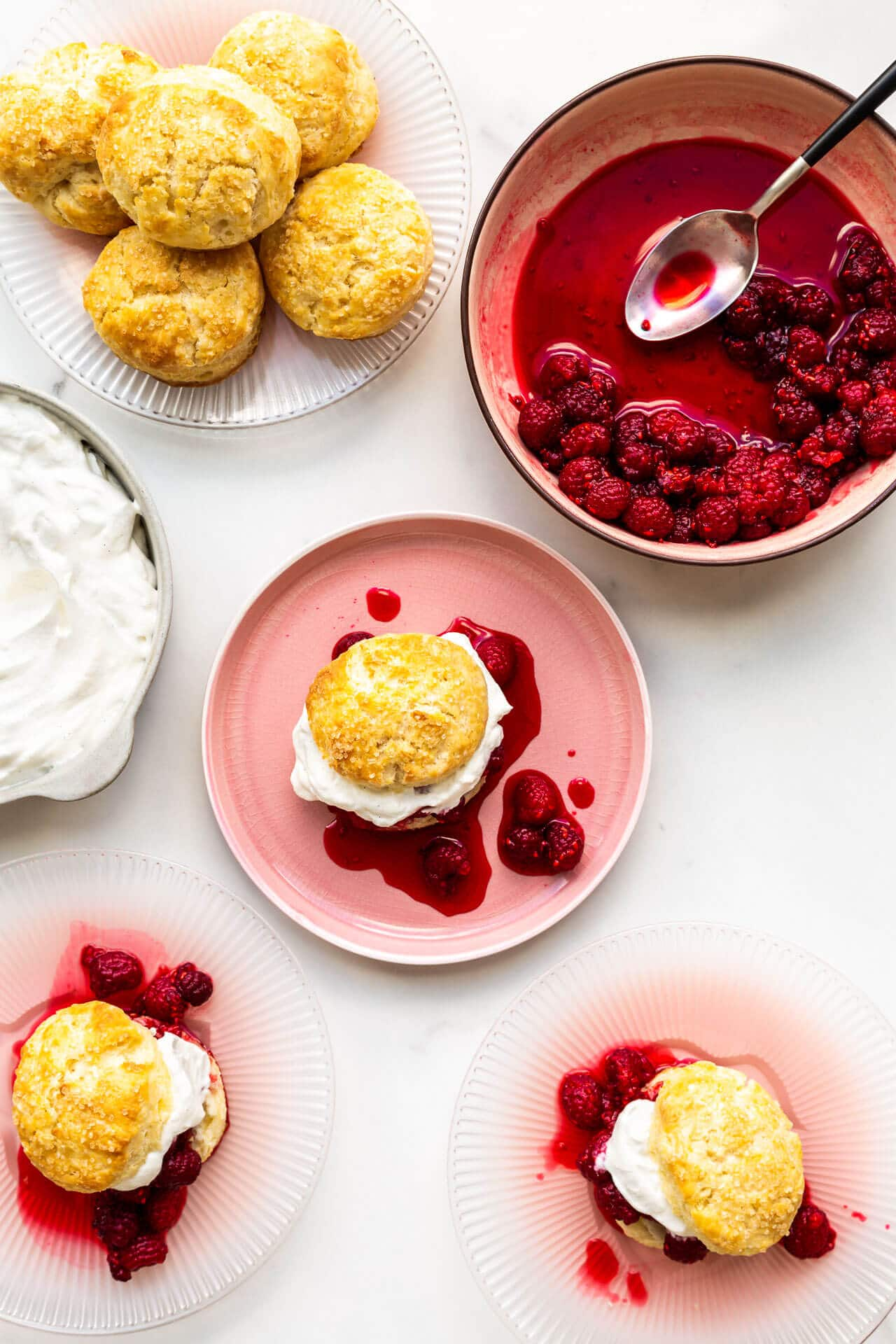 Assembling raspberry shortcakes with biscuits, macerated berries, and whipped cream