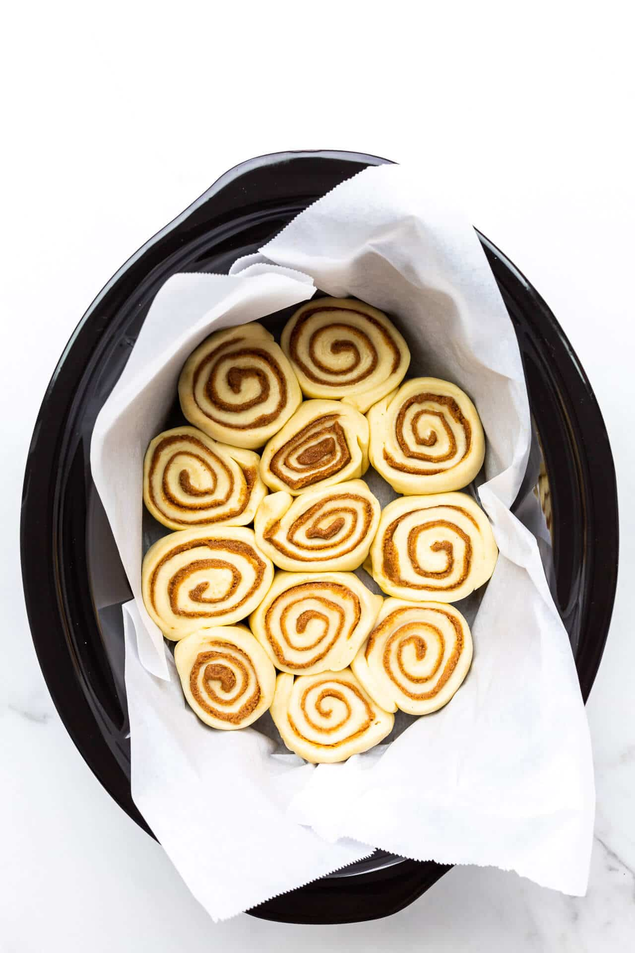 Cinnamon buns placed in a parchment-lined slow cooker black ceramic insert ready to be baked