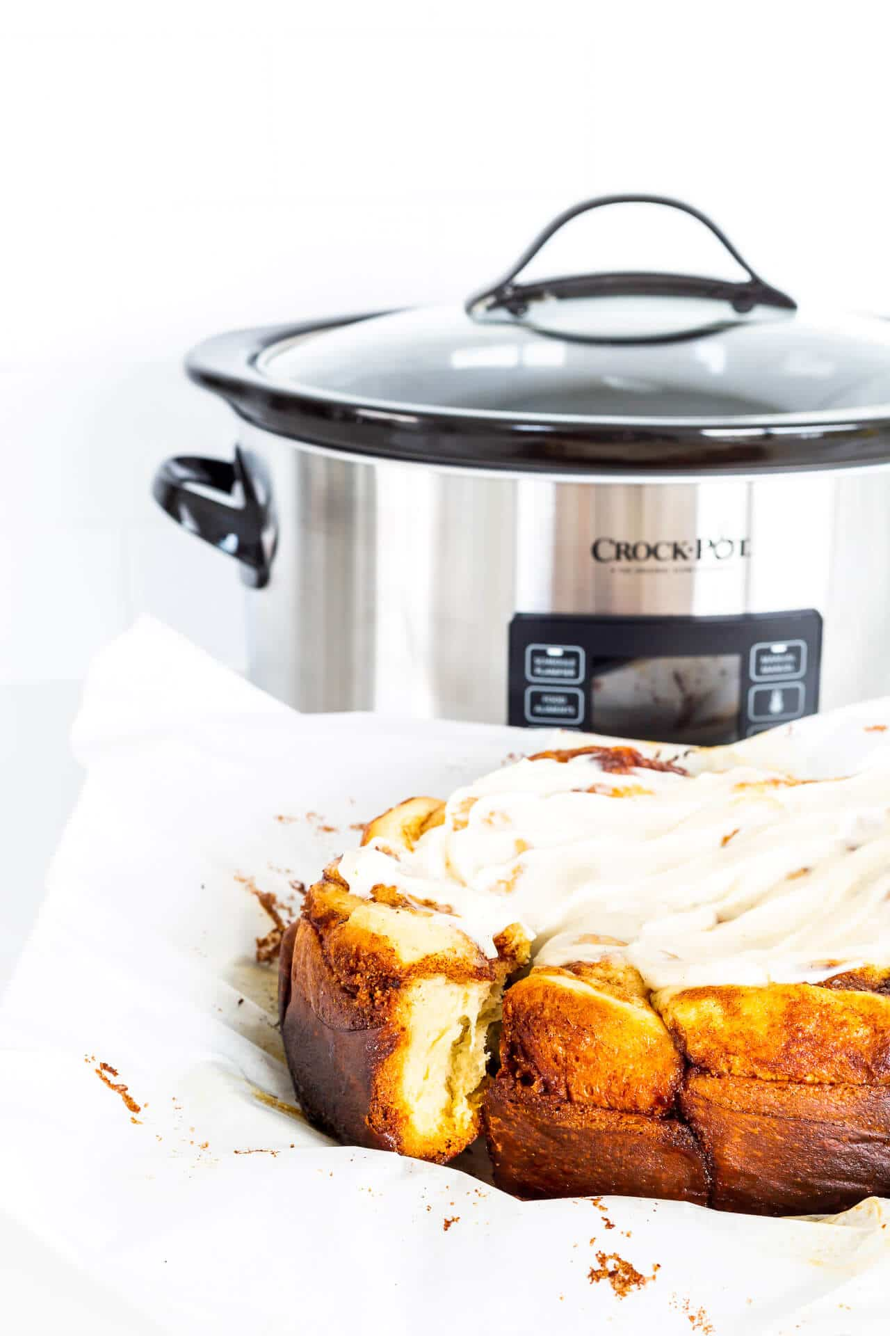 Frosted Crock-Pot cinnamon rolls freshly baked next to the slow cooker they were baked in