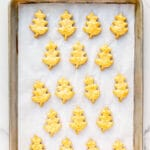 Freshly baked cheese shortbread cookies shaped like oak leaves on a parchment-lined baking sheet