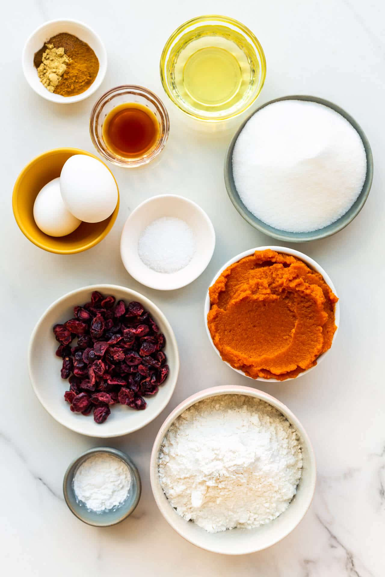 Ingredients to make pumpkin bread with dried cranberries measured out into little bowls