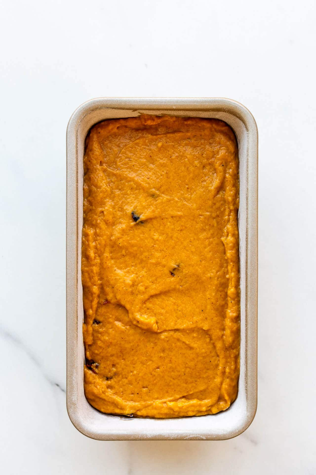 Pumpkin cranberry bread in a loaf pan before baking