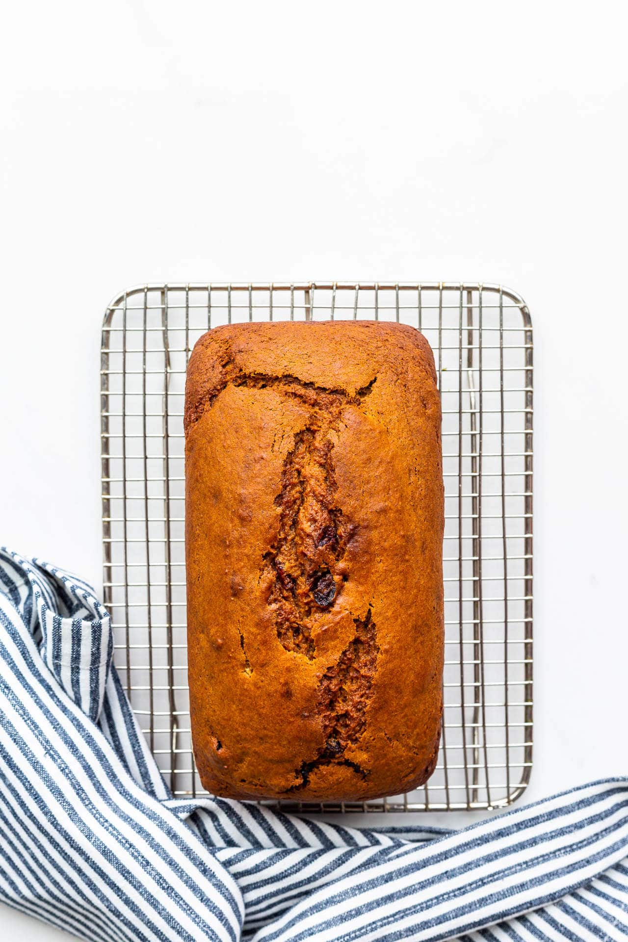 Pumpkin cranberry bread cooling on a wire rack with a striped linen