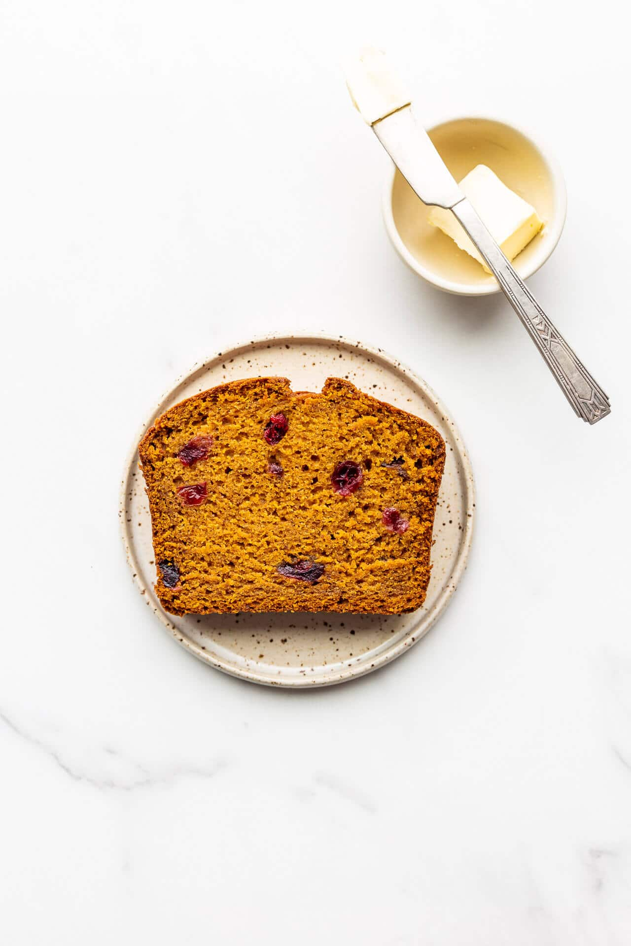 A slice of pumpkin cranberry bread on a speckled plate with a little bowl of butter and a knife