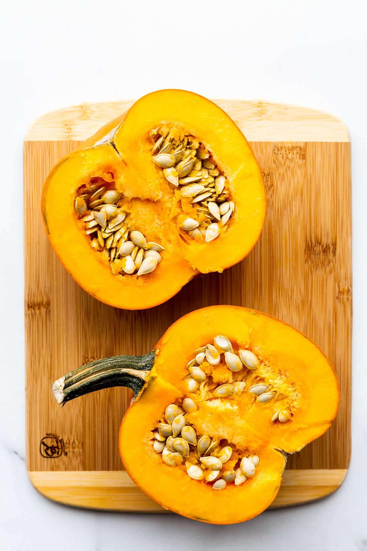 Sugar pie pumpkin cut in half to reveal flesh and seeds on a wood cutting board.