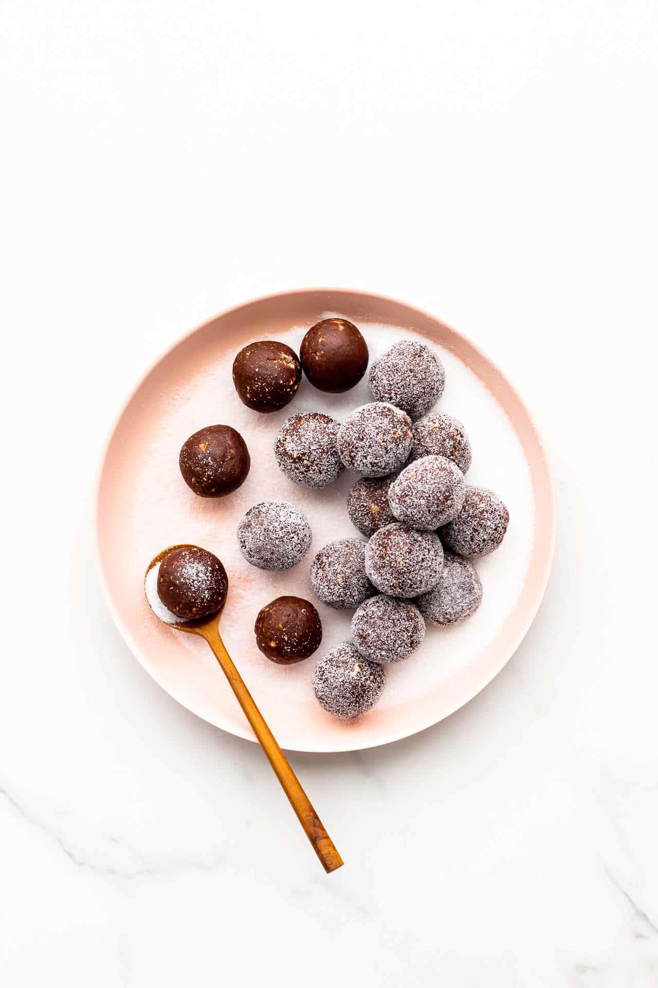 Coating amaretto balls in granulated sugar.