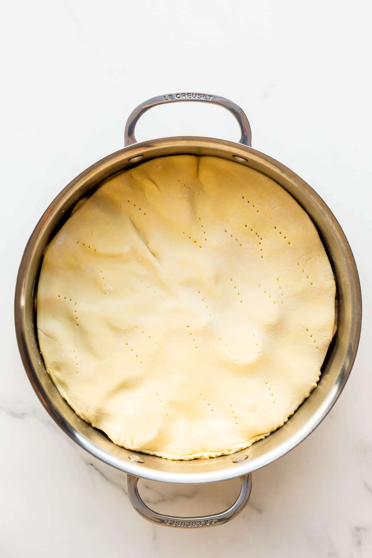 A pan with apples topped with pastry ready to be baked to make an apple tarte tatin.