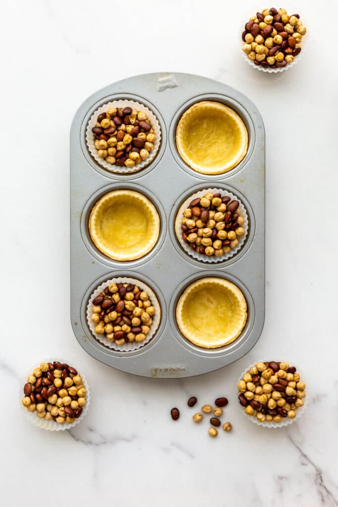 Blind baking tart shells in a muffin pan, using silicone muffin liners and dried beans to weigh down the crust.