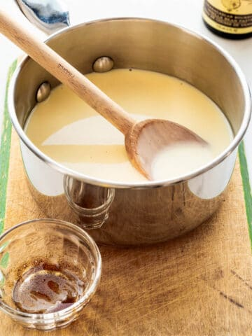 A saucepan of homemade crème anglaise (custard sauce) that is flavoured with vanilla bean paste.