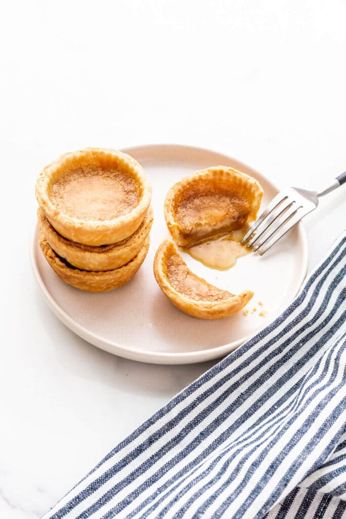 A beige plate with a stack of three butter tarts and a fourth next to it, cut open with a fork to reveal the gooey filling.