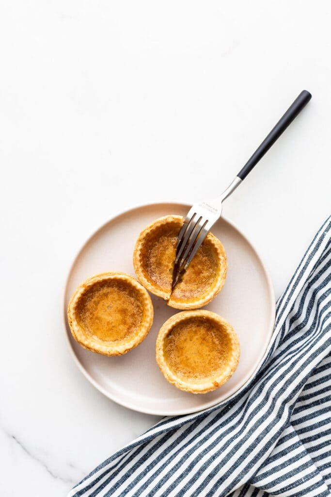 A beige plate with three butter tarts on it and a fork cutting open one of them.
