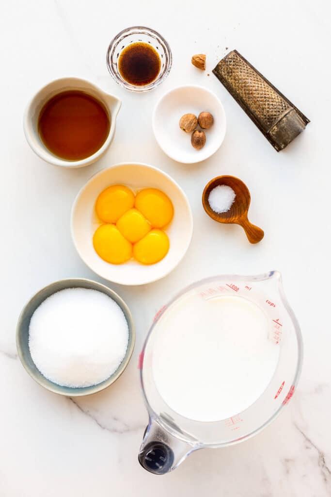Ingredients measured out to make homemade eggnog from simple ingredients, including egg yolks, sugar, milk, salt, nutmeg, rum, and vanilla bean paste..