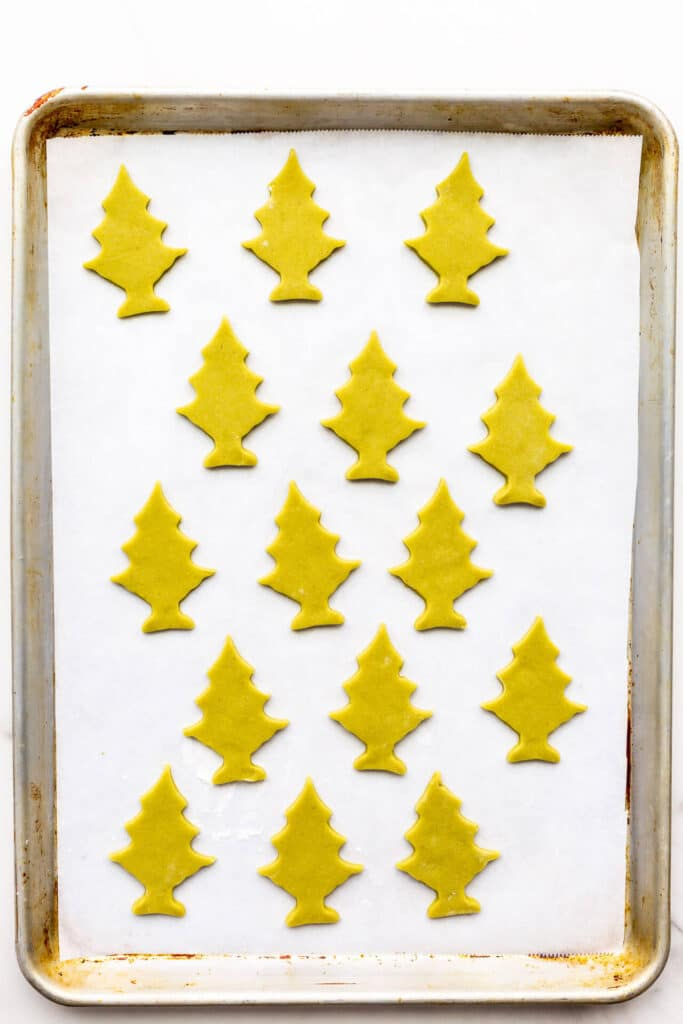 Matcha cookies cutout in tree shapes on a sheet pan lined with parchment paper.