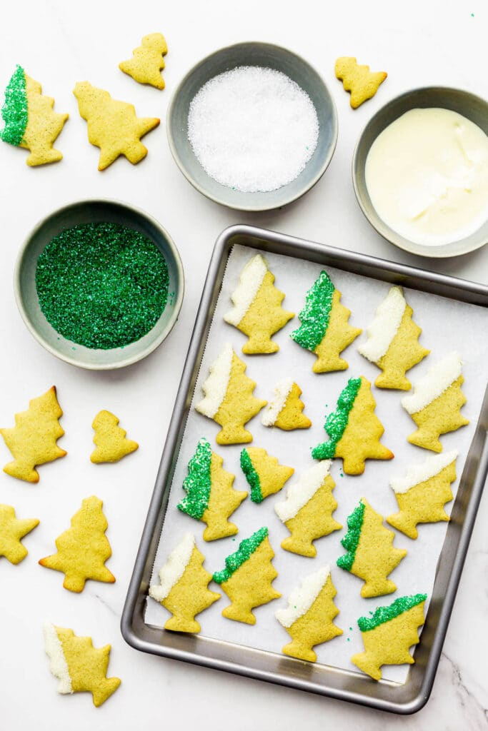 Dipping matcha green tea gingerbread cookie cutouts shaped like trees in white chocolate and coloured sugar sprinkles.