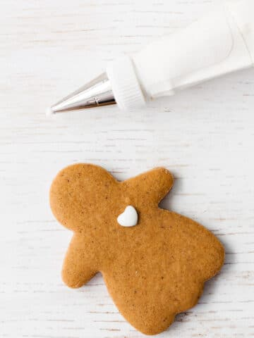 Decorating a gingerbread cookie with royal icing using a piping bag and a fine tip.