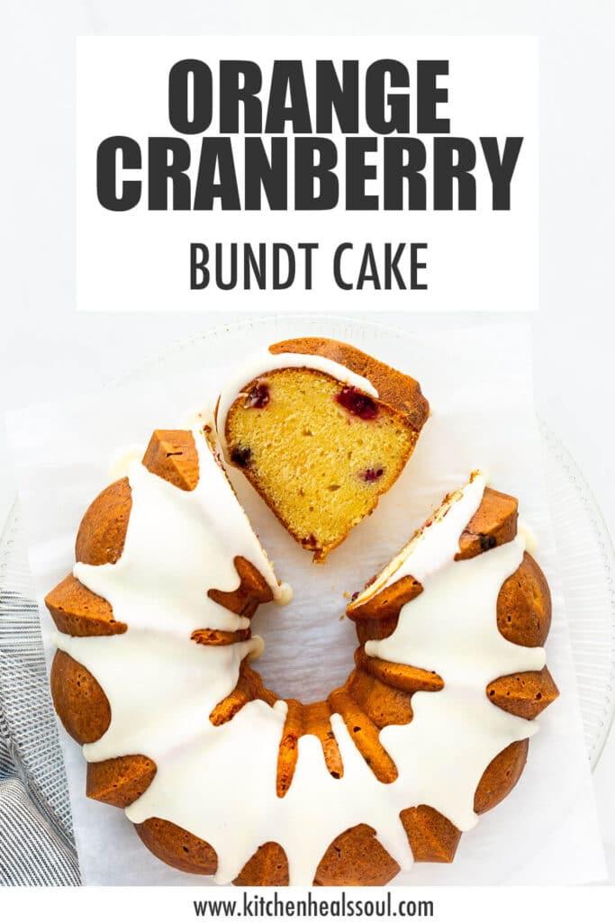 Glazed orange cranberry bundt cake sliced on a serving plate.