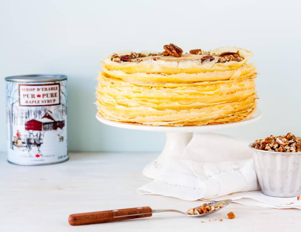 A tall crêpe cake on a cake stand topped with chopped pecans with a can of maple syrup in the background