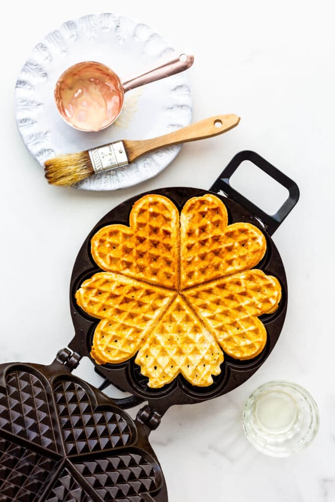 Plain waffle being cooked in a waffle maker.