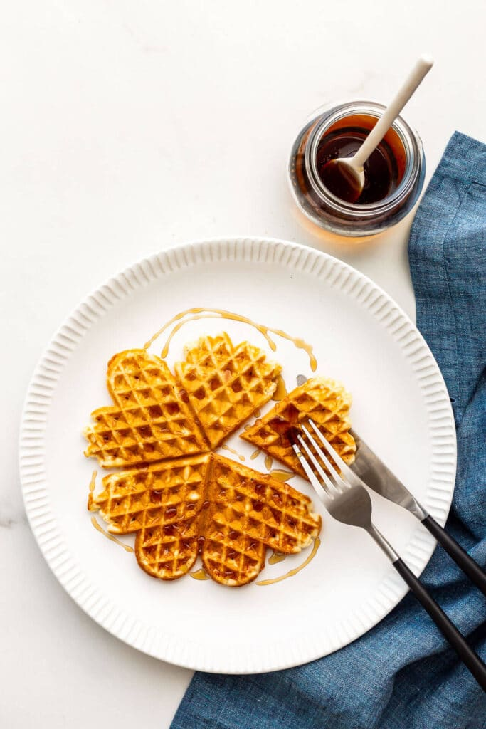 Waffle on a white plate with maple syrup and a blue linen napkin.