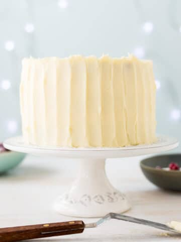 Thick cream cheese frosting on a layer cake, spread with an offset spatula to create vertical streaks on the surface of the frosting.