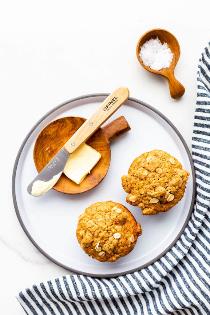 Banana muffins on a grey plate with butter and a butter knife, and sea salt.