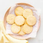 A pink plate filled with lemon shortbread cookies and with a yellow napkin.