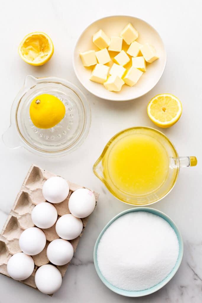 Ingredients for lemon curd measured out, including butter, lemon juice, sugar, and eggs.