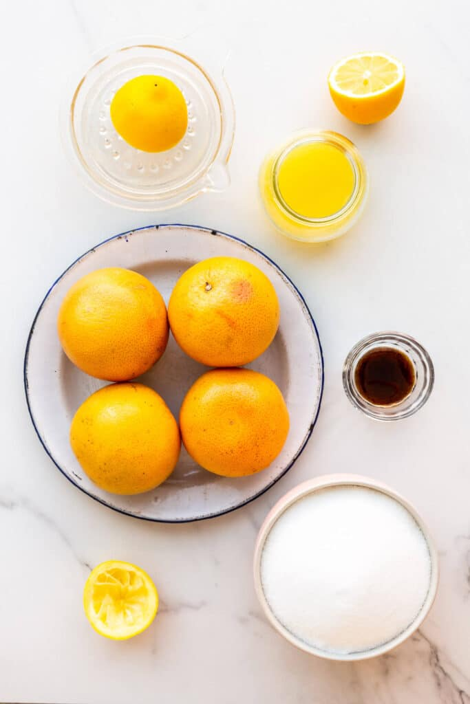 Ingredients to make homemade grapefruit marmalade from scratch, including whole pink grapefruit, lemon juice, sugar, and vanilla bean paste.