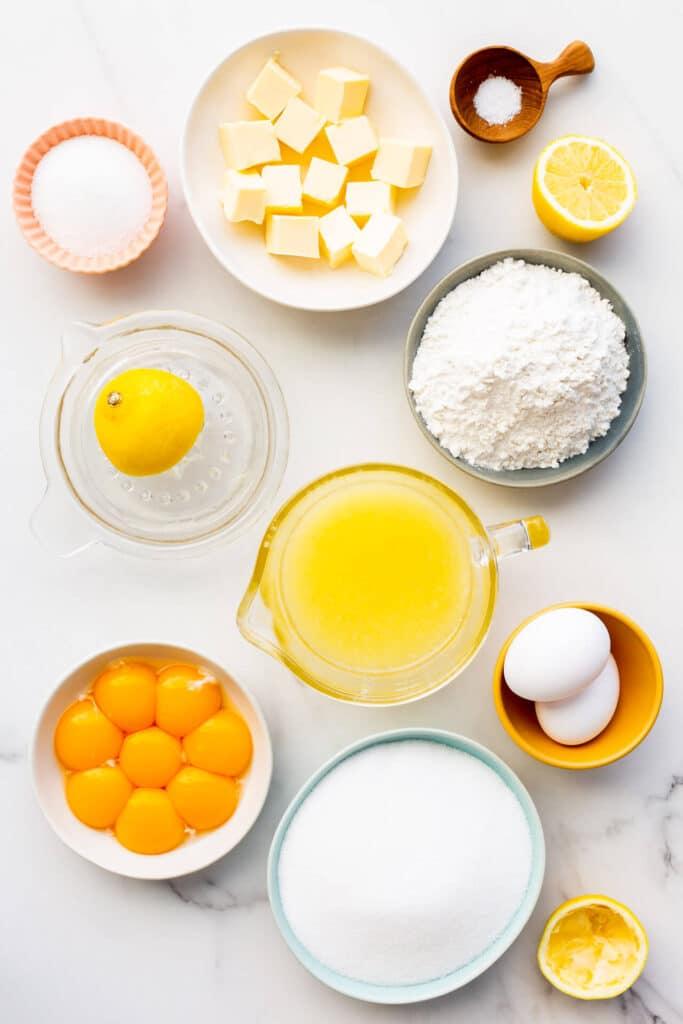 Ingredients to make lemon bars from scratch measured out, including butter, sugar, salt, lemons, lemon juice, flour, eggs and egg yolks.