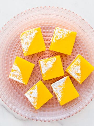 A pink glass plate with lemon bars.