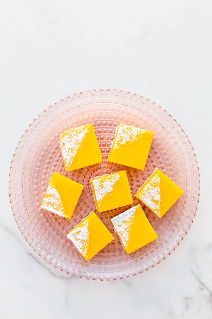 A pink glass plate with lemon bars topped with powdered sugar, ready to serve.