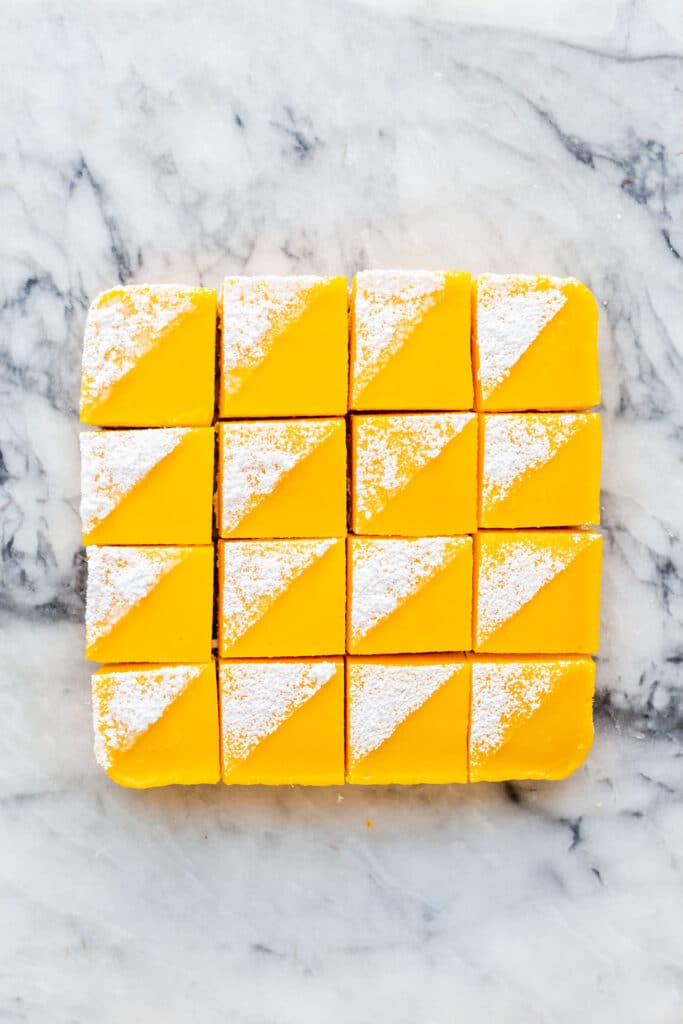 Lemon bars cut into squares and decorated with icing sugar on a marble surface.
