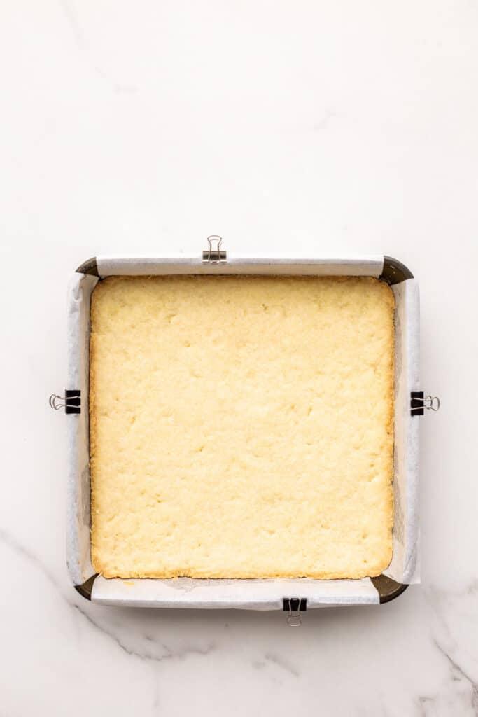 Baked shortbread crust base for lemon bars, ready for the lemon filling to be poured on top.