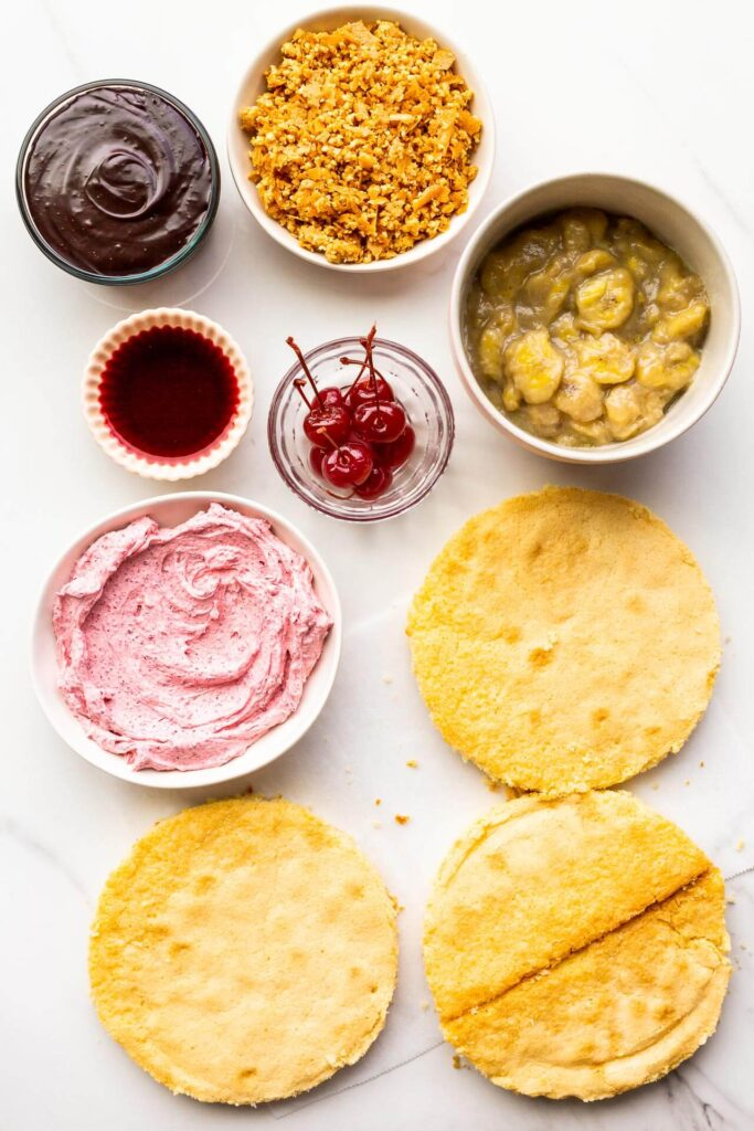 The components of a banana split cake, ready to be stacked and assembled into a layer cake, including three layers of vanilla cake, cherry frosting, maraschino cherries, cherry juice, banana compote, peanut crunch, and chocolate fudge sauce.