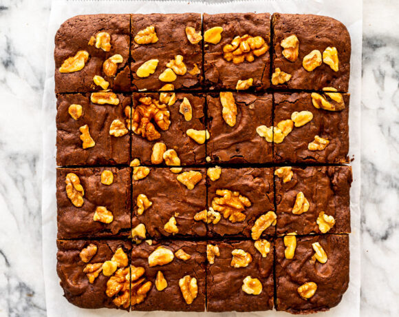 Brownies with walnuts cut into squares on a marble surface.