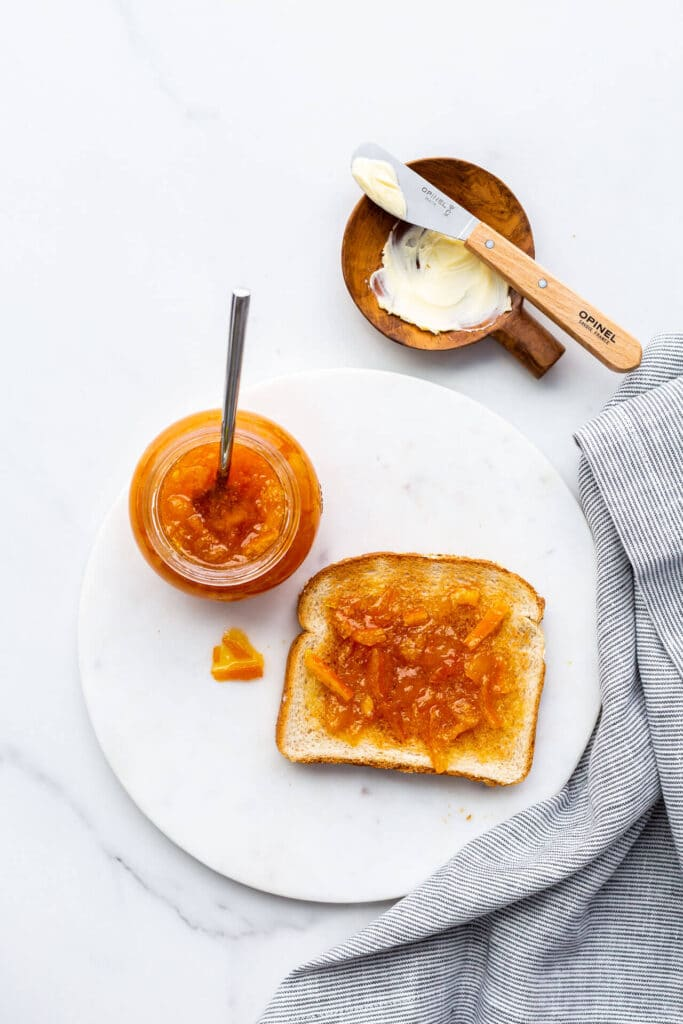 A piece of toast topped with orange marmalade.