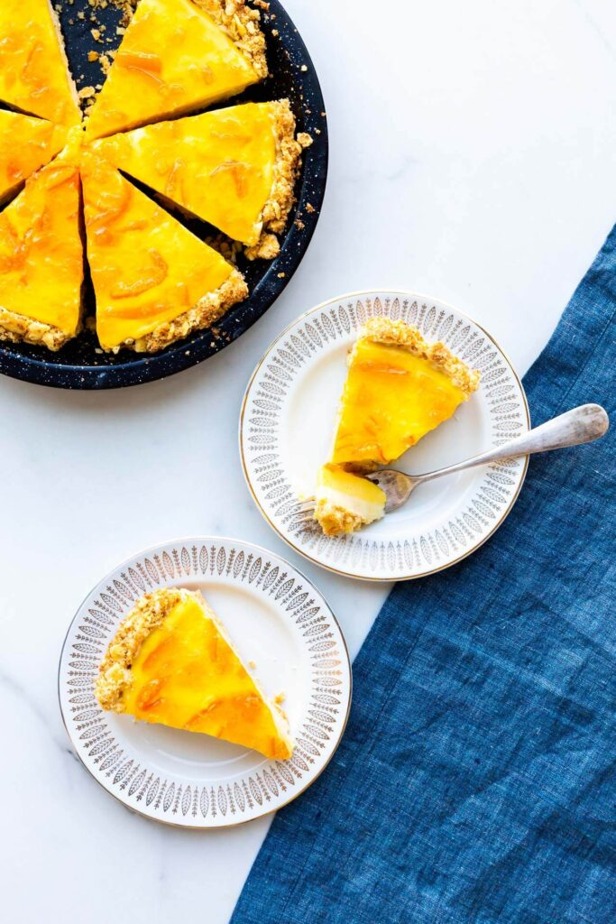 Orange curd pie sliced and served on small dessert plates.