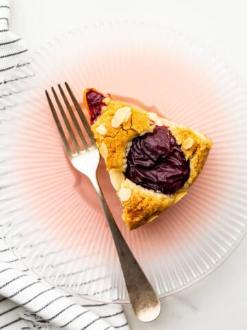 A slice of plum cake on a pink glass plate.