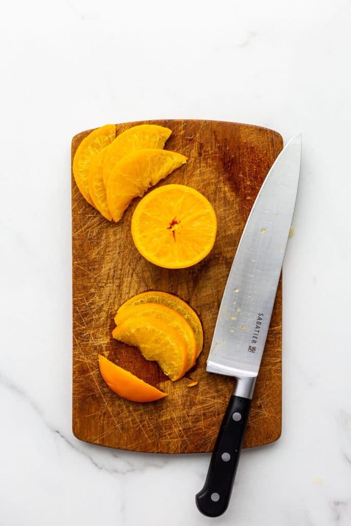 Slicing boiled oranges to make orange marmalade.