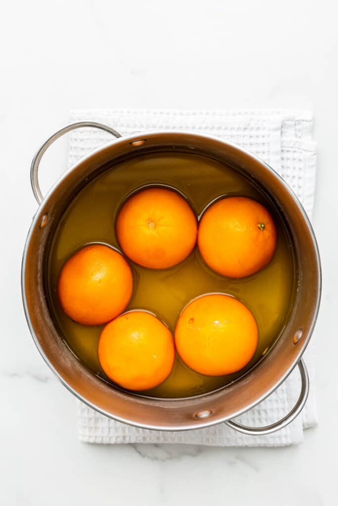 A pot of boiled oranges, ready to be sliced and transformed into orange marmalade.