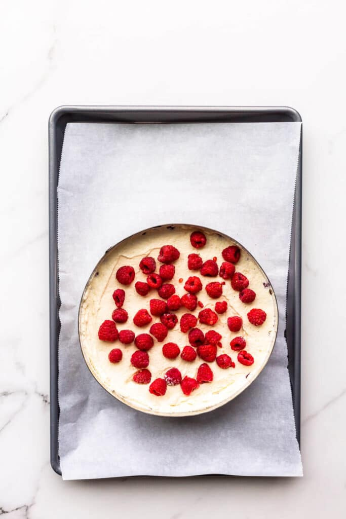 Filling a framboisier cake in a cake ring with mousseline cream and fresh raspberries.