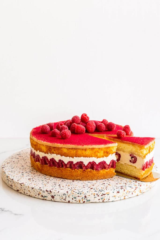 Framboisier cake topped with fresh raspberries on a terrazzo board being served with a gold cake lifter.