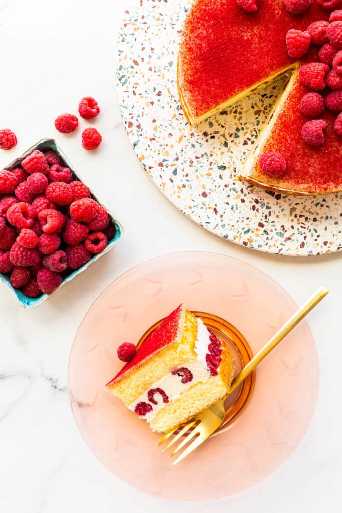 A slice of framboisier cake on a pink glass plate with a gold fork.