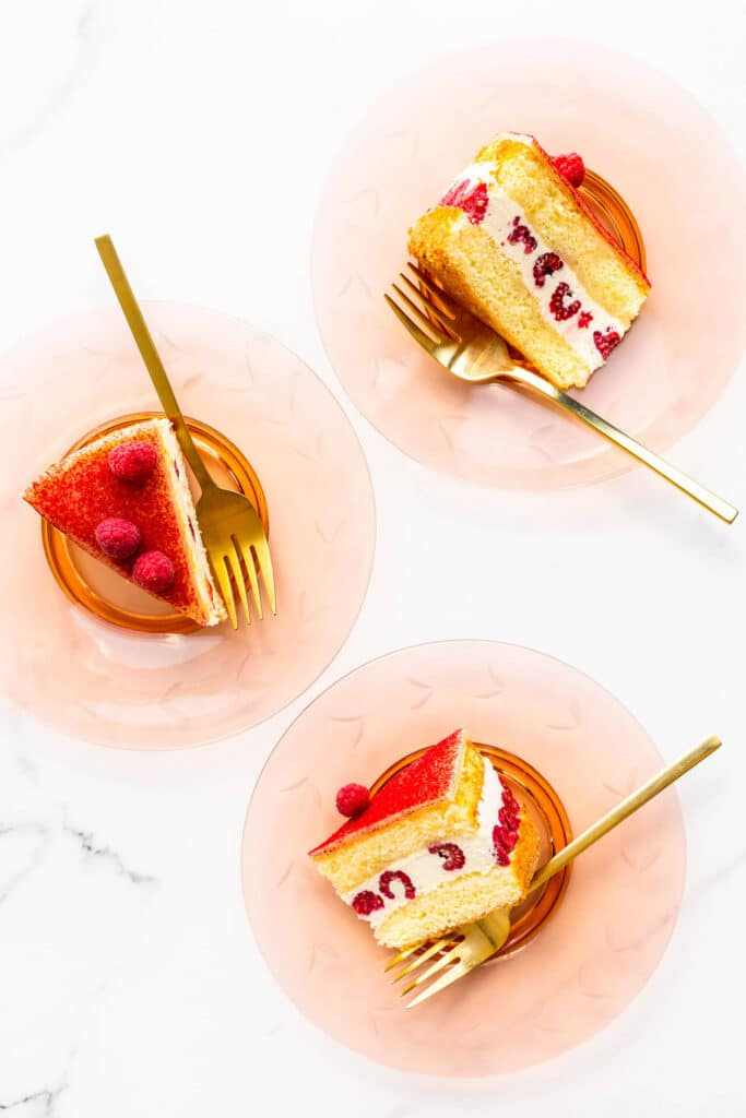 Slices of raspberry and cream layer cake served on glass plates with gold forks.