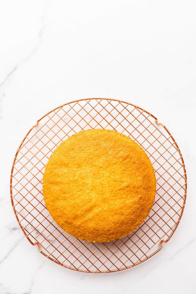 Sponge cake cooling on a wire rack.